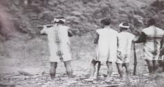 布農巒社。玉里。進行射耳祭。四人皆著傳統服飾,但每人背心不同,左一背心全為直條紋。