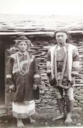 盛裝打扮的南布農族郡社新高頭目夫婦。男子著布製頭飾、琉璃製頸飾、袖套、胸兜,加掛三角形腹袋,下身圍一條前遮片,再外穿無袖上衣,綁腿布、赤足。