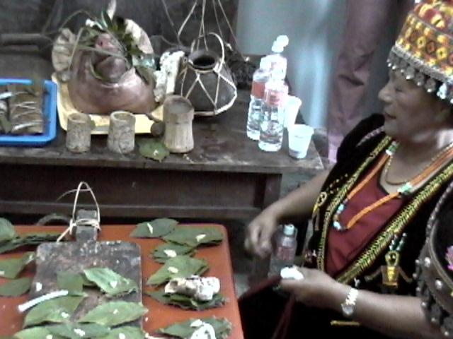 東排灣族五年祭女巫師(朱連金)在祖靈像前以祭葉,帶骨的碎豬肉,小米糕和小米酒祭告祖靈