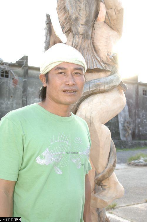 於木雕前站立的阿美族男性